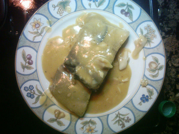 there it is the bacalao al pil pil served on the plate, ready to eat with crusty bread